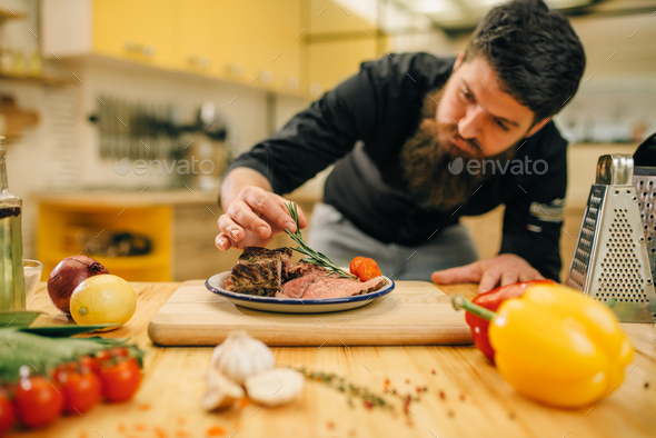 Chef decorates herbs roasted meat slices in plate - Stock Photo - Images