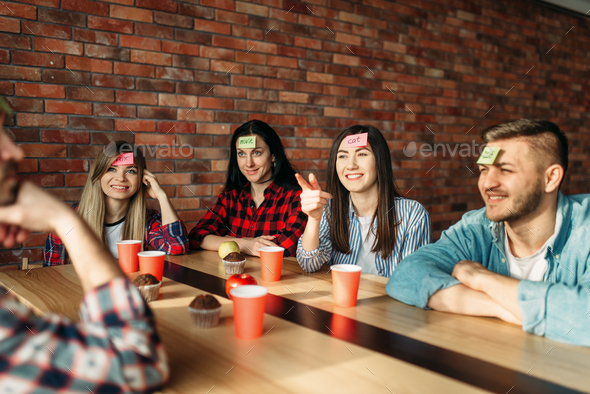 Smiling friends playing sticker notes to forehead - Stock Photo - Images