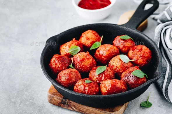 Homemade beef or chicken meatballs in tomato sauce in a frying pan - Stock Photo - Images