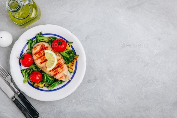 Grilled salmon steak and baked vegetables. Tomato, broccoli, zucchini with salmon fillet. Top view - Stock Photo - Images