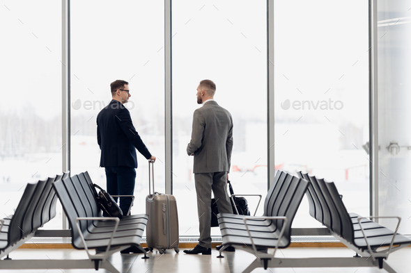 Silhouette of two businessman standing in front of a big window at airport at wating area near - Stock Photo - Images
