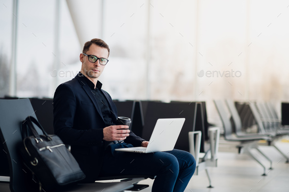 A business man sitting at the airport park working with his laptop and drinking takeaway coffee - Stock Photo - Images