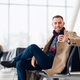 Attractive young adult man in stylish scarf and coat sitting inside airport terminal waiting area - PhotoDune Item for Sale