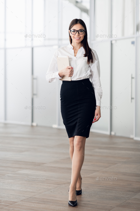 Smiling businesswoman walking along the office corridor with a tablet computer - Stock Photo - Images