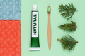 Bamboo toothbrush with natural toothpaste and towels on green background top view - PhotoDune Item for Sale