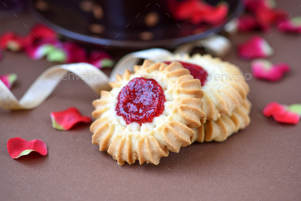 Shortbread cookies with jam in the middle on plate against brown - Stock Photo - Images