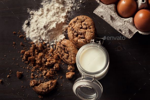 Top view of Homemade chocolate chip cookies with bottle of milk, white flour, fresh eggs and crumbs - Stock Photo - Images