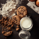 Top view of Homemade chocolate chip cookies with bottle of milk, white flour, fresh eggs and crumbs - PhotoDune Item for Sale