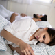 Beautiful young wife texting with lover on smartphone while husband is sleeping - PhotoDune Item for Sale