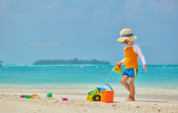 Three year old toddler playing on beach - Stock Photo - Images