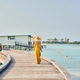Woman in dress walking on tropical beach boardwalk - PhotoDune Item for Sale