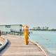 Woman in dress walking on tropical beach boardwalk - PhotoDune Item for Sale