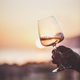 Rose wine in hand with sunset and sea at background - PhotoDune Item for Sale
