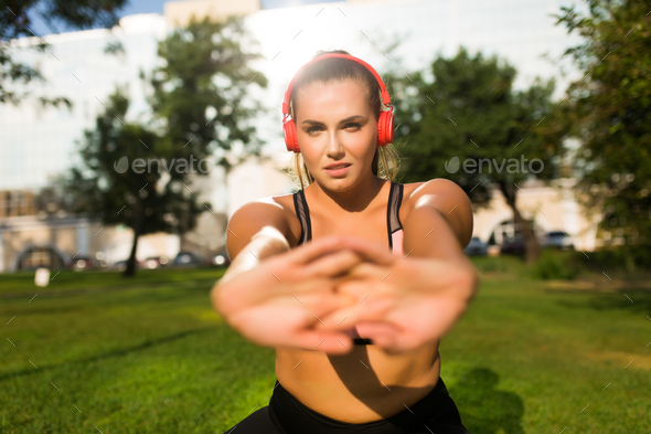 Close up young plus size woman in sporty top with red headphones - Stock Photo - Images