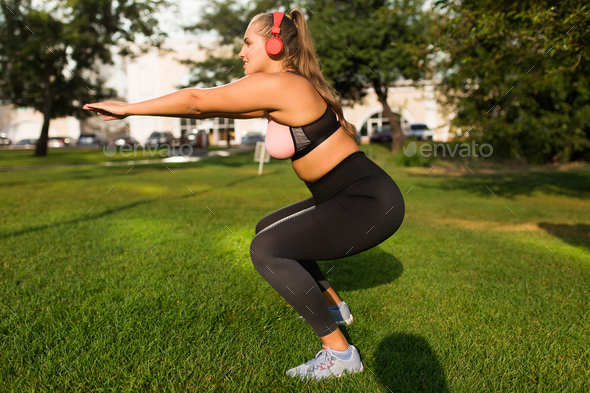 Young attractive plus size woman in sporty top and leggings with - Stock Photo - Images