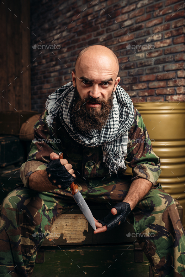 Terrorist with knife sits on boxes of ammunition - Stock Photo - Images