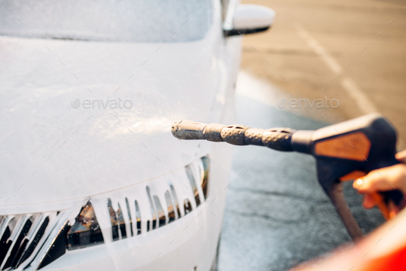 Female person wash off the foam from car - Stock Photo - Images