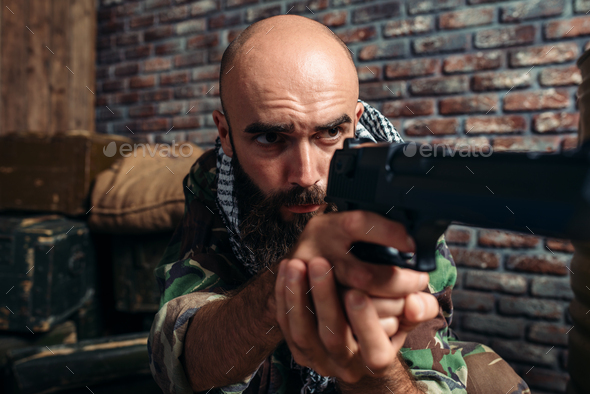 Bearded terrorist in uniform aiming from a gun - Stock Photo - Images