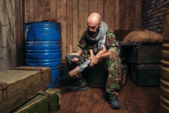 Terrorist inserts magazine into kalashnikov rifle - Stock Photo - Images