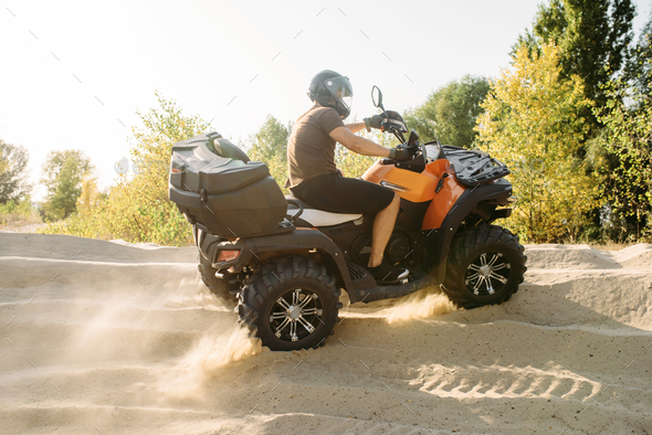 Atv riding in sand quarry, dust clouds, quad bike - Stock Photo - Images