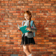 Cute schoolgirl with schoolbag reading a textbook - PhotoDune Item for Sale