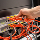 Close-up of Male Technician Plugging Network Cable In Network Router - PhotoDune Item for Sale