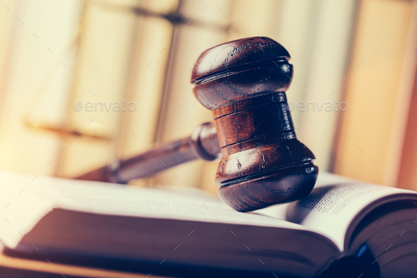 Court hammer laying on book. - Stock Photo - Images