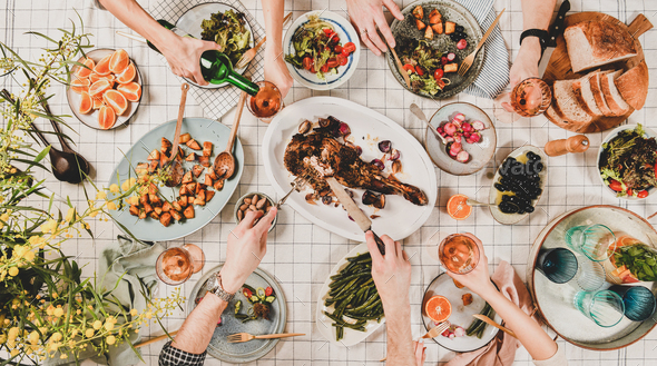 Flat-lay of hands of people eating and drinking rose wine - Stock Photo - Images