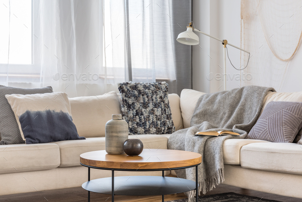 Round wooden coffee table in front of scandinavian corner sofa with pillows