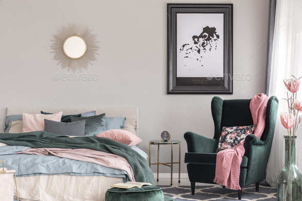 Floral pillow and pink blanket on emerald green comfortable armchair in  fashionable bedroom