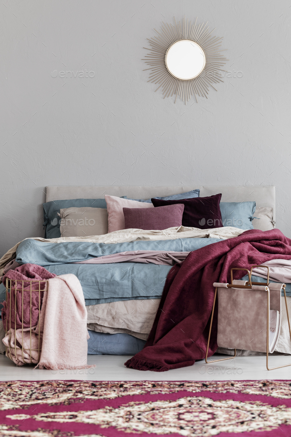 Colorful pillows and burgundy blanket on comfortable bed in fashionable bedroom interior - Stock Photo - Images