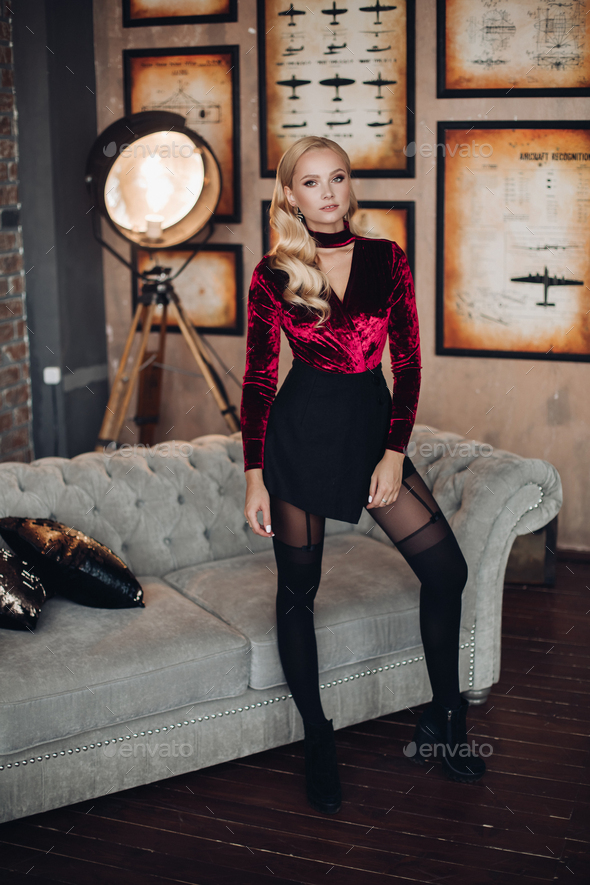 Sexy young blonde woman in stylish evening dress and tights at sofa - Stock Photo - Images