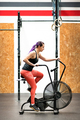 Fit young woman working out on an exercise bike - PhotoDune Item for Sale