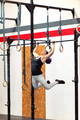 Fit young woman doing pull-ups on rings - PhotoDune Item for Sale