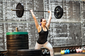 Young woman performing a clean and jerk exercise - PhotoDune Item for Sale