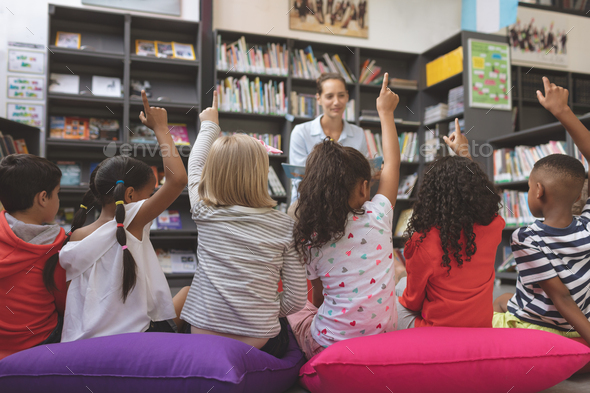 Schoolkids raising hand to answer at a question asking agaisnt bookshelf - Stock Photo - Images
