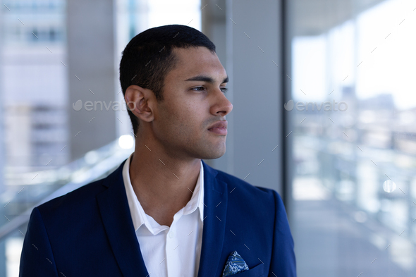 Front view of thoughtful young mixed-race businessman looking away standing in modern office - Stock Photo - Images