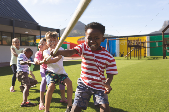 Front view of multi ethnic group of happy school kids playing tug of war in playground - Stock Photo - Images