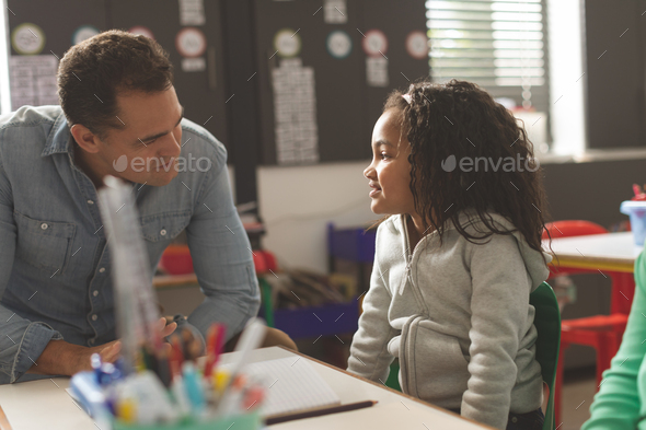 Front view of a teacher interacting with school girl while sitting in classroom at school - Stock Photo - Images