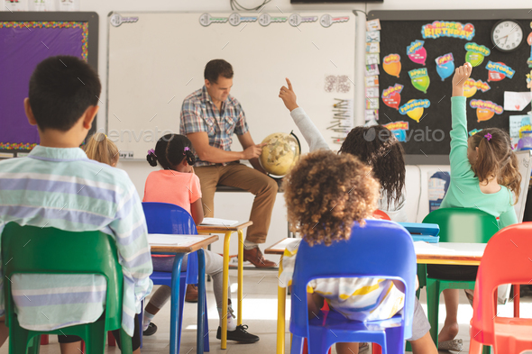 schoolteacher learning at his pupils the earth globe in classroom at school with school kids - Stock Photo - Images