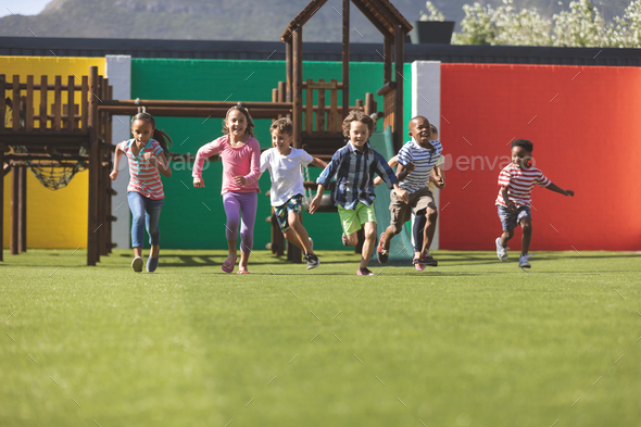 Front view of multi ethnic students running in school playground - Stock Photo - Images