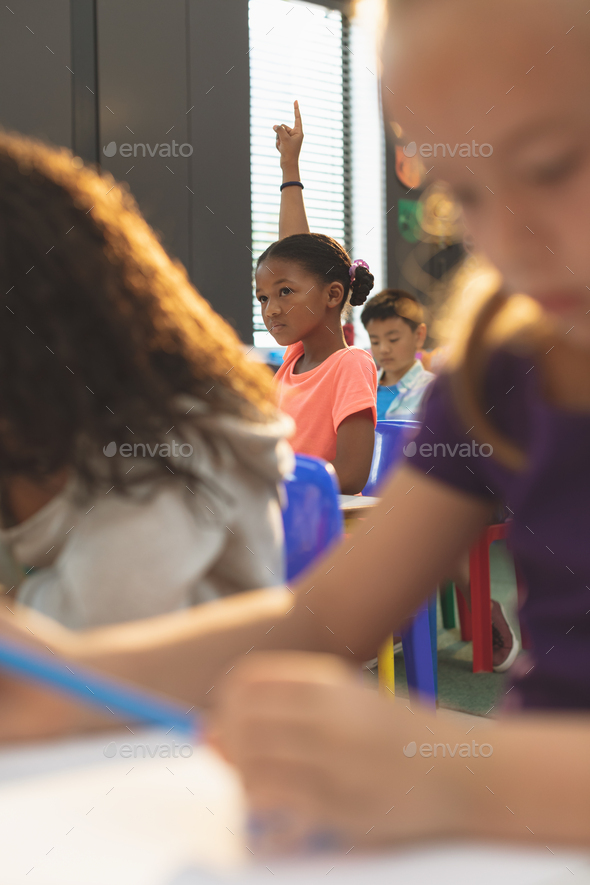 Front view of a schoolgirl raising hand while sitting in classroom at school - Stock Photo - Images
