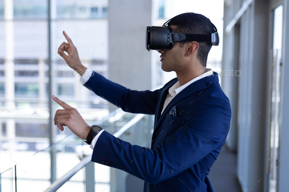 Businessman using virtual reality headset standing in modern office - Stock Photo - Images