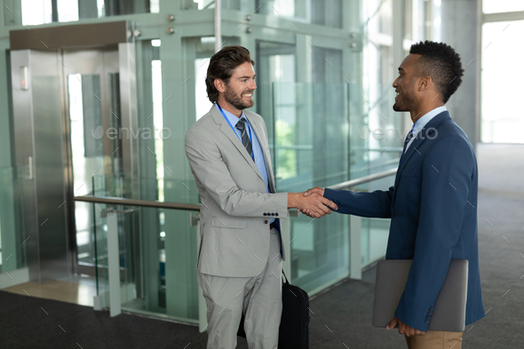 Young diverse businessmen shaking hands with each other in the modern corridor at office.  - Stock Photo - Images