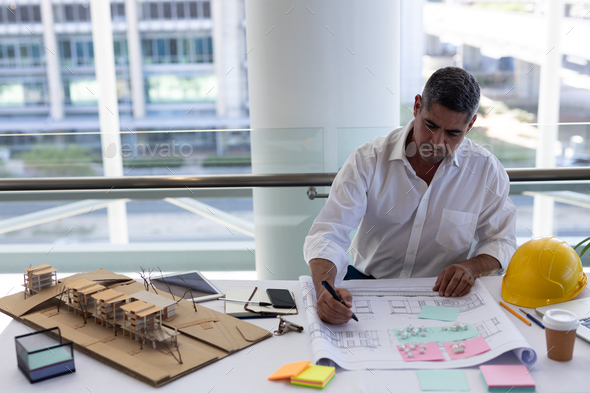 Front view of handsome mature Caucasian male architect working at desk in modern office - Stock Photo - Images