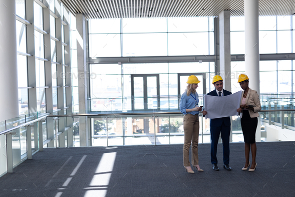 Front view of multi-ethnic architects discussing over blueprint in modern office - Stock Photo - Images