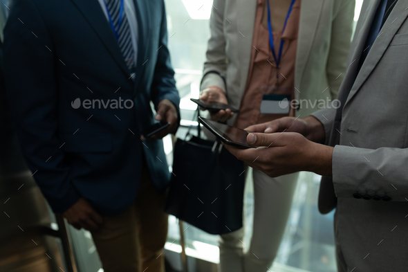 Mid section of young multi-ethnic business colleague discussing over the digital tablet in elevator - Stock Photo - Images