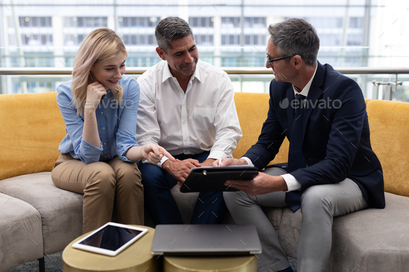 Business executives discussing over digital tablet sitting on the sofa in modern office - Stock Photo - Images