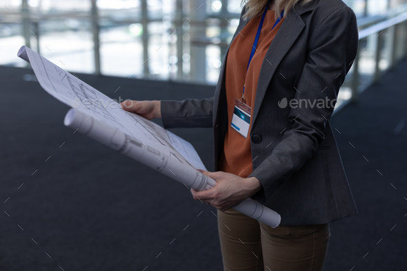 Mid section of young blonde Caucasian female architect holding blueprint in modern office - Stock Photo - Images