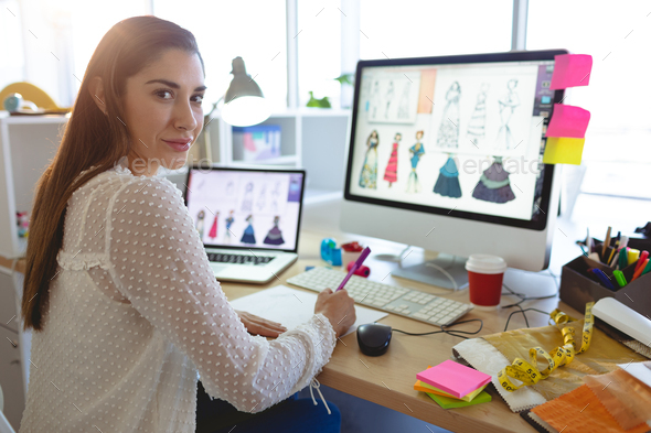 Young Caucasian Female Fashion Designer Looking At Camera While Working At Desk In A Modern Office Stock Photo By Wavebreakmedia